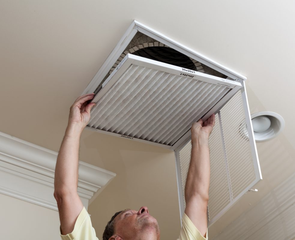 man opening air conditioning filter in ceiling